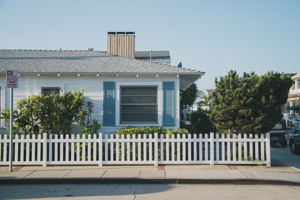 A blue house with a white picket fence