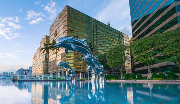 A dolphin fountain in front of a hotel