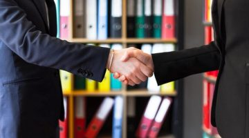 Two business shaking hands after signing a business loan deal