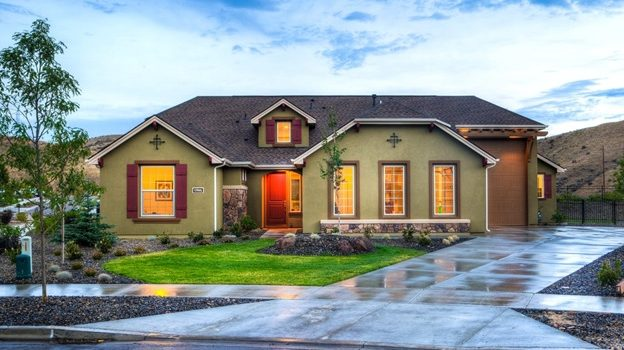 A beige house with the lights on and a glistening driveway
