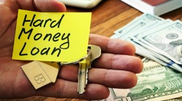 A man holding a hard money loan sign and house keys