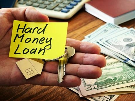 A man holding a hard money loan sign and house keys