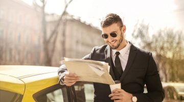 A suited man happily holding a newspaper and coffee