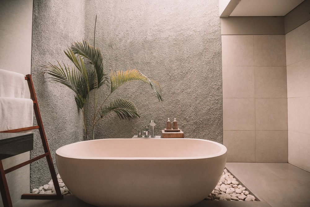 Japanese-style bathroom with ivory bathtub and pebbles