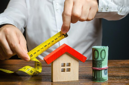 A professional home appraiser measuring the size of a house