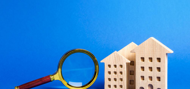 A magnifying glass and wooden house model