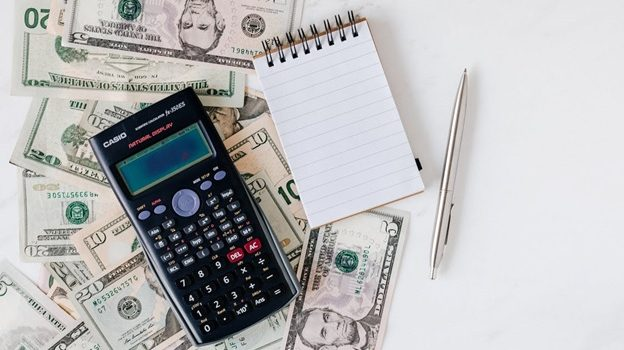 A calculator and notepad over a stack of U.S. dollars