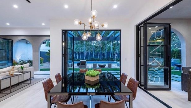 The interior of a house with classic iron French doors opened and showing the backyard lawn and pool
