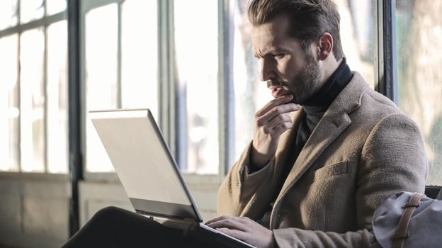 A man thinking while working on his laptop