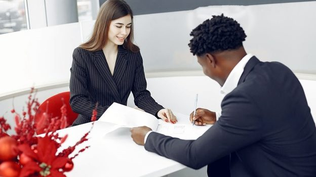A woman helping her client sign a contract