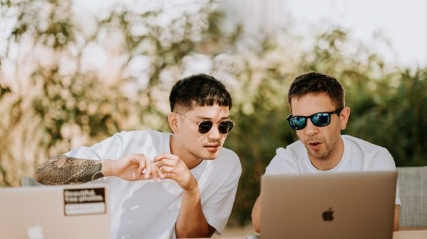Two men discussing and working on their laptops