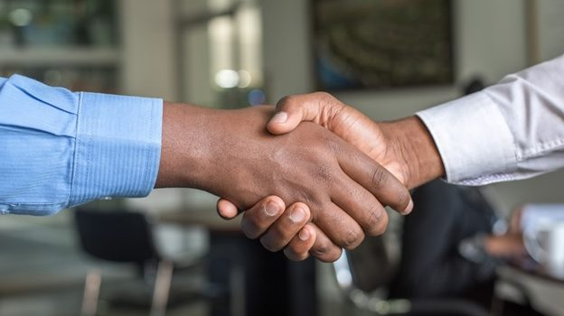 Two people shaking hands after a deal