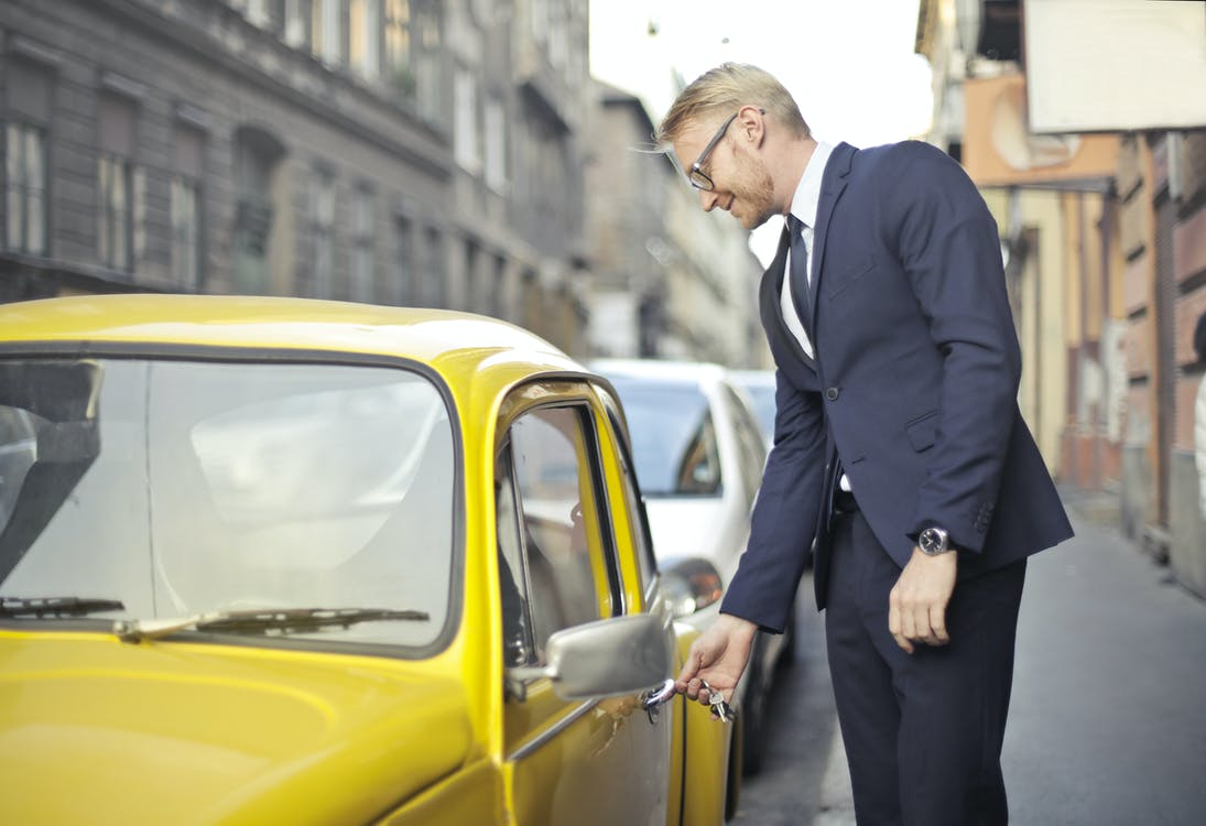 A man in a suit trying to unlock a yellow car with keys.