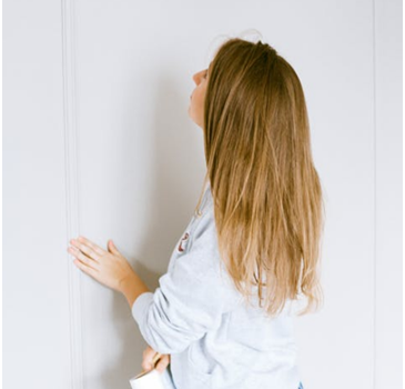 A female brown-haired home inspector in Palm Beach wearing a white hoodie and blue jeans is touching a white wall as part of home inspection services in Palm Beach