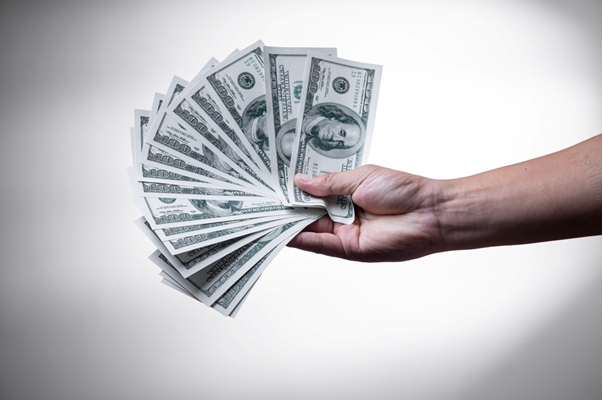 A person holding cash in hand