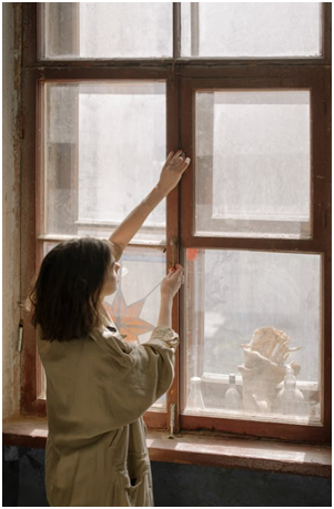 A woman is inspecting a home's window