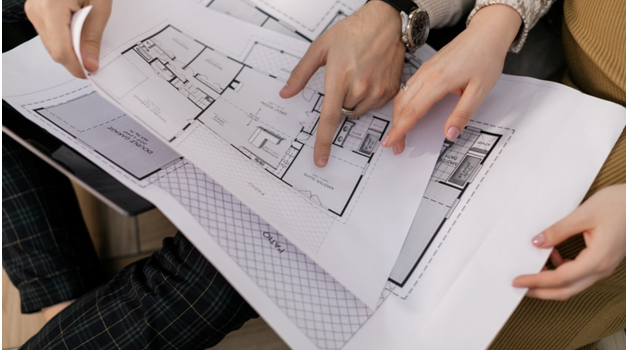 Hands of two people holding property maps
