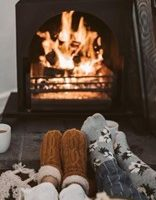 people snuggling in front of a fireplace in winter