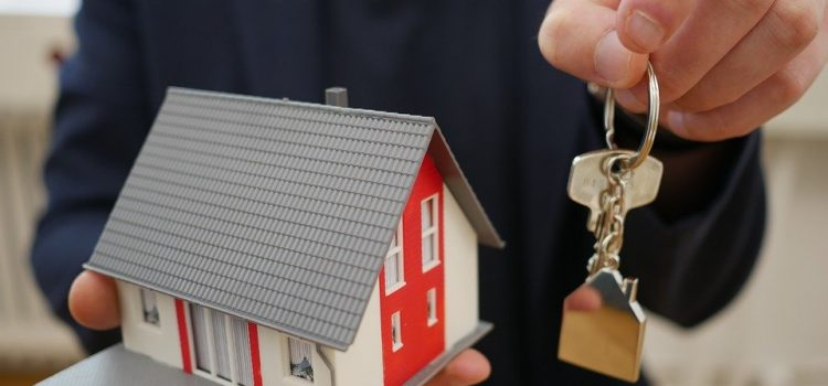 man holding model house and keys