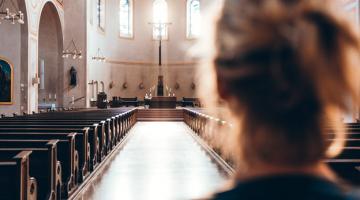 A woman standing inside a church in California