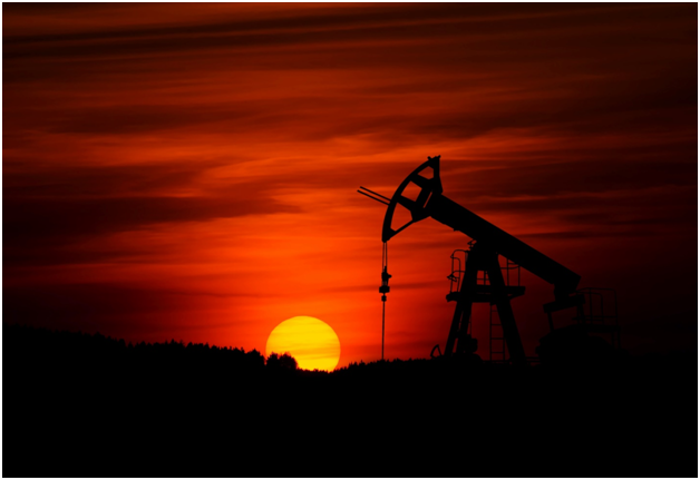 Oil drilling during a sunset.