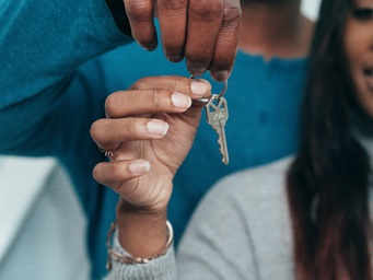 couple giving the keys after selling house for cash