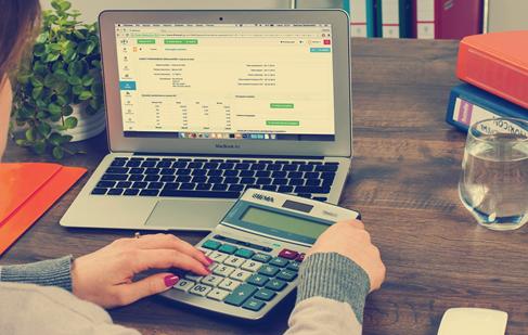 A person calculating through a calculator and a laptop