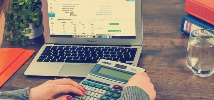 A professional bookkeeper with a MacBook Air and a calculator
