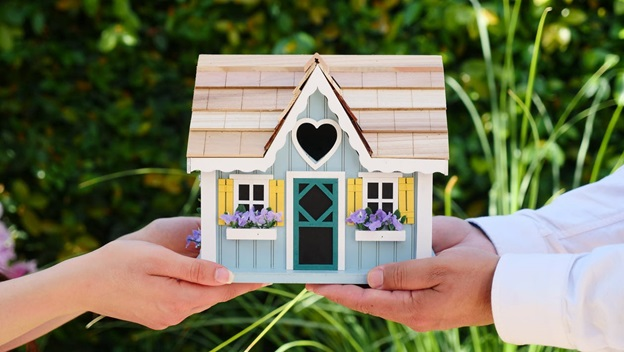 A couple is holding a miniature house