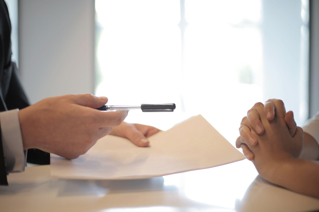 Two people exchanging contract and pen