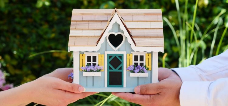 Two people holding a small house