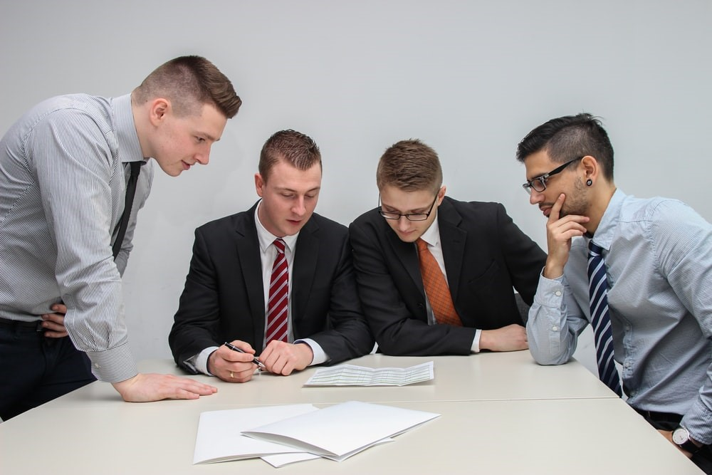 four people reading a document